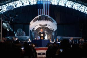 Viceprezident USA Mike Pence hovoří o aktuálních plánech Trumpovy administrativy v plánovaných letech na Měsíc a dál. V pozadí raketoplán Discovery, Smithsoniánské muzeum. Foto: NASA/Joel Kowsky