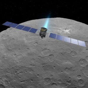 Tento obrázek tvoří počítačová vizualizace sondy Dawn, která je však zasazena do skutečného snímku trpasličí planety Ceres, který pořídila sonda Dawn.