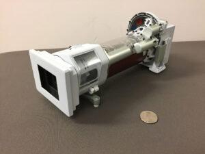 Na 3D tiskárně vytvořený model kamery Mastcam-Z - na fotce je i americký čtvrťák pro představu o velikosti.