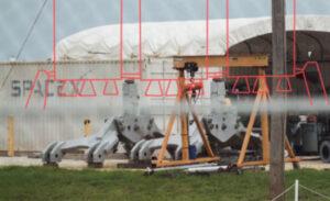 Vzpěry pro Falcon Heavy vyfocené na floridském kosmodormu - snímek je doplněn o grafiku zobrazující, kde se budou dotýkat Falconu Heavy.
