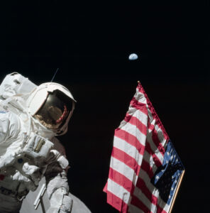Harrison Schmitt pózuje s americkou vlajkou při výstupu na lunární povrch v rámci mise Apollo 17.