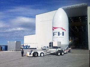 Aerodynamický kryt pro premiéru Falconu Heavy. Přes otevřená vrata haly HIF můžeme tušit obrysy Falconu Heavy.