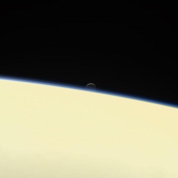 Saturnův aktivní a oceánem disponující měsíc Enceladus se schovává za obří planetou na rozlučkovém snímku mezinárodní sondy Cassini. Snímek vznikl 13. září společně s několika dalšími fotkami. Sonda k němu použila svou kameru s úzkým zorným polem a nasnímala Enceladus ze vzdálenosti 1,3 milionu kilometrů, přičemž Saturn byl 1 milion kilometrů daleko. Rozlišení na povrchu Enceladu je 8 km/pixel a snímek vznikl složením fotek pořízených přes červený, zelený a modrý filtr, aby bylo dosaženo přirozených barev. Projekt Cassini-Huygens byl společným podnikem NASA,ESA a Italské kosmické agentury.