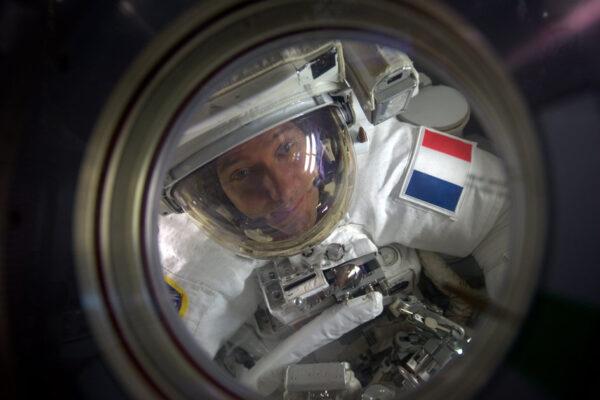 """Francouzský astronaut Thomas Pesquet v přechodové komoře během svého prvního výstupu do volného prostoru – 13. ledna 2017. Společně s americkým kolegou, kterým byl Shane Kimbrough, strávili mimo stanici 5 hodin a 58 minut. Jejich úkolem byla výměna vnějších baterií, které ukládají energii pro provoz stanice. Sám Thomas k této fotce napsal: """"Američanka Peggy Whitson má rekordní počet výstupů a několikrát byla také IV (osoba, která se stará o to, aby se astronauti dostali na výstup a zase zpátky). Dostala nás ven o hodinu dříve oproti plánu a ještě udělala tuhle fotku! Je skvělé mít takové kolegy."""""""