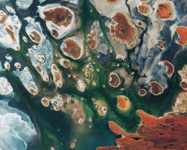 """Hnědé kopce doplňují satelitní snímek východoaustralského jezera Lake MacKay. Nachází se na hranicích států Západní Austrálie a Severní Teritorium. Jedná se o solné jezero, které má vodu pouze po období dešťů a to navíc jen někdy. K tomu, aby se v něm udržela voda, potřebuje srážky, čímž se liší od sezónních jezer, která udrží vodu déle. Téměř polovina australských řek ústí do vnitrozemí a často končí v takovýchto jezerech. Zelené a modré barvy na snímku ukazují rozložení řas, vlhkých půd a minerálů (většinou soli). Na některých hnědých """"ostrovech"""" a na pobřeží vpravo dole můžeme vidět písečné pruhy v západně-východním směru. Jezero leží na okraji Velké písečné pouště, která pokrývá 285 tisíc kilometrů čtverečních. Silnice jsou v této oblasti vzácné a nejčastěji je využívají dobrodruzi na čtyřkolkách. Mezi hlavní silnice patří Canning Stock Route, která leží zhruba 300 kilometrů západně od snímku, nebo Tanami Track, která spojuje Stuart Highway s Great Northern Highway a leží zhruba 300 kilometrů východně. Snímek zachytila 15. března družice Sentinel 2B. V té době byla stále v kalibrační fázi (od startu uplynulo jen 8 dní), ale přístroje již posílaly první fotky a ukazovaly své schopnosti snímkování pevniny, pobřeží a jezer. Po plném zprovoznění byly tyto prostředky zdarma zveřejněny pro široké spektrum uživatelů."""