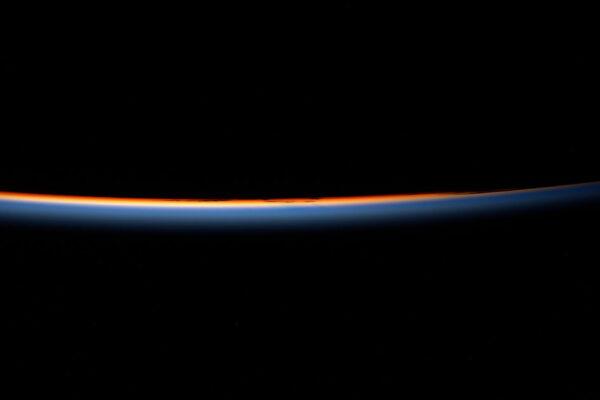"""Svítání z oběžné dráhy vyfocené Thomasem Pesquetem z paluby ISS ukazuje zemskou atmosféru. Sám Thomas k tomu napsal: """"Východ Slunce. Zažíváme jej každý den 16×, protože ISS oběhne Zemi za 90 minut a pohybuje se rychlostí 28 800 km/h. Samozřejmě nevidíme všechny východy Slunce, protože většinou pracujeme uvnitř, ale vždy a znova bych mohl pořizovat takovéto fotky."""""""