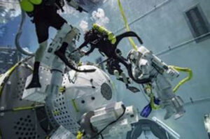 Astronauti v bazénu NBL nacvičují manipulaci s přechodovou komorou firmy NanoRacks.
