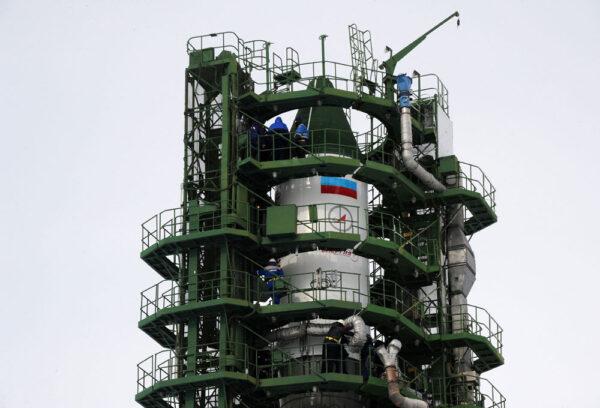 Dvě poloviny obslužné věže obklopují raketu a technici kontrolují všechny systémy.