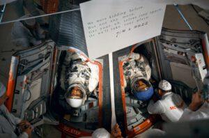 Básnička Lovella a Aldrina zavěšená nad kokpitem v den startu.
