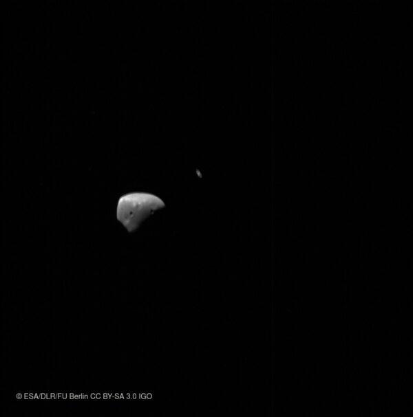 Deimos a za ním procházející Saturn