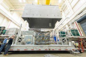 Snímek z Goddardova střediska - technici spouští kryt kontejneru.