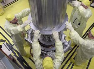 Technici spouští kryt na testovaný exemplář systému KRUSTY. Zpod krytu byl následně odčerpán vzduch, aby byly podmínky srovnatelné s kosmickým prostředím.