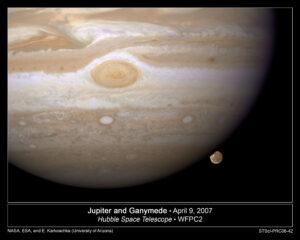 Hubbleův teleskop vyfotil měsíc Ganymed, jak se schovává za Jupiterem.