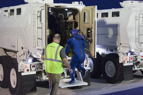 Astronauti okamžitě nastupují do zaparkovaných obrněných vozidel Mine-Resistant Ambush Protected vehicle.