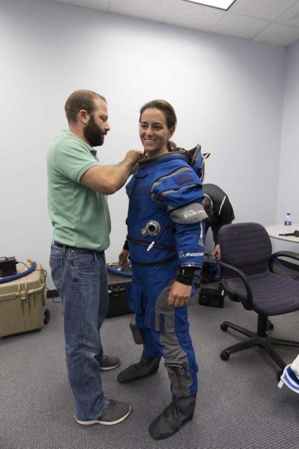 Nicole Aunapu Mann během oblékání skafandru Boeingu Blue před zkouškou evakuace.