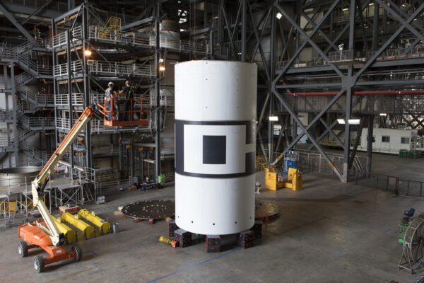 """3.8.2018 - Sestavený kryt nosiče pro AA-2, nazvaný """"aeroshells"""", v sekci HB4 budovy VAB. Tento exemplář bude použit pro testy sestavení hardwaru i pro samotný let. Důvodem pro vznik krytu je aerodynamické napodobení průměru zakrytovaného servisního modulu Orionu a zvýšení hmotnosti nosiče ATB pro napodobení zrychlení SLS."""