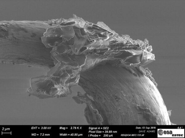 Mikroskopická fotografie zrnka prachu, které odebrala sonda Hayabusa z asteroidu Itokawa.