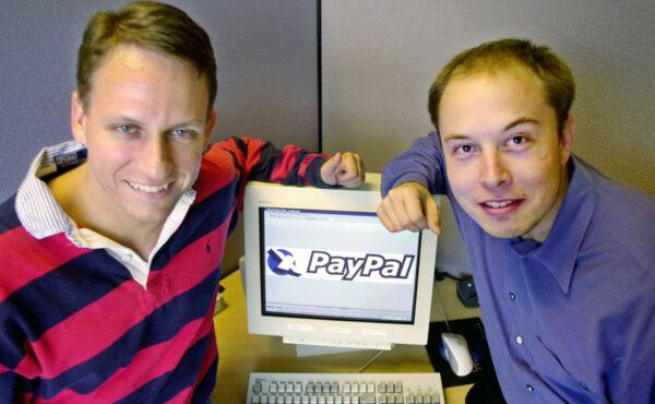 Výkonný ředitel firmy PayPal Peter Thiel a zakladatel Elon Musk pózují u loga své firmy v centrále v kalifornském Palo Altu.
