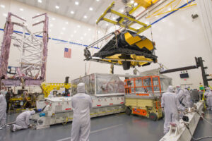 V popředí vidíme vykládání optické části teleskopu s vědeckými přístroji, v pozadí je složený servisní modul se složeným slunečním štítem.