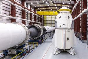 Crew Dragon pro nepilotovanou misi DM-1 v montážní hale vedle rakety Falcon 9 pro tuto misi.