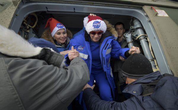 Američanka po přeletu na Bajkonur vystupuje z vrtulníku