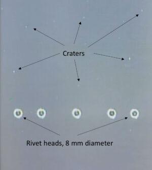 Stopy po impaktech přírodních i uměle vytvořených objektů na modulu Columbus. Rozměry můžeme srovnat s hlavičkami nýtů o průměru 8 milimetrů.