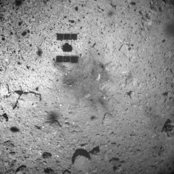 Hayabusa 2 se už vzdalovala od Ryugu a byla 30 metrů nad terénem, když pořídila tuto fotografii, na které je vidět její stín i stopy po zážehu trysek pro odlet.