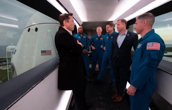 Elon Musk, administrátor NASA Jim Bridenstine a čtyři astronauti před startem Crew Dragonu v interiéru přístupové lávky do lodě.