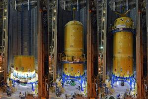 Fotografie zachycující postupnou montáž přední sestavy centrálního stupně CS-1 v buňce D. Buňka D byla převedena do programu SLS po ukončení programu Space Shuttle. Má jedinou, svisle se pohybující pracovní plošinu