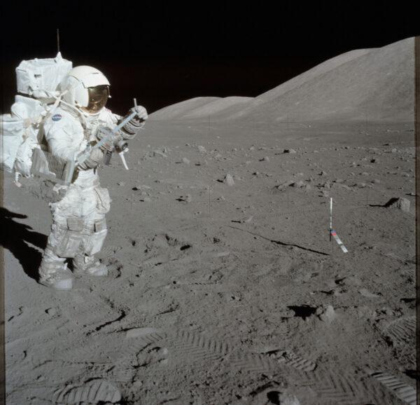 Harrison Schmitt při kosmické vycházce Apolla 17 pracuje s nástrojem pro odběr vzorků.