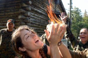 Christina se raduje ze zapálení ohně při nácviku přežití astronautů po přistání v divočině.