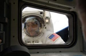 Spokojený Mike Massimino pózující před oknem letové paluby po vyčerpávající opravě přístroje STIS.
