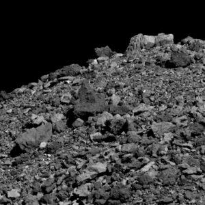 Povrch Bennu je posetý kameny a balvany. Tento snímek pořídila 28. března kamera PolyCam ze vzdálenosti 28 metrů. Snímek pokrývá oblast širokou 49,6 metru. Světlý balvan v horní části měří na výšku 4,8 metru.