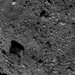 Snímek pořízený 4. dubna kamerou PolyCam zachycuje v levém dolním rohu velmi tmavý balvan a vlevo nahoře oblast, která by mohla být vhodná pro odběr vzorků.