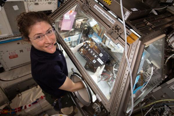 Christina Koch při práci s gloveboxem na ISS.