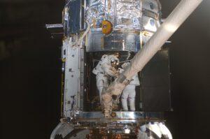 """Michael """"Bueno"""" Good na konci robotické paže a Michael """"Mass"""" Massimino uvnitř teleskopu při opravě přístroje STIS."""