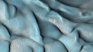 Mars je pokrytý neustále se pohybujícím pískem. Duny najdeme na mnoha místech - některé mají jen pár metrů, jiné se počítají na stovky metrů. Tento snímek pochází ze sondy MRO, konkrétně z její kamer HiRiSE. Snímek má upravené barvy, aby lépe vynikl tvar dun, jejich složení a pohyb.