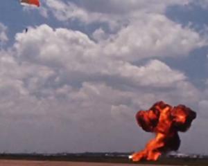 LLRV vybuchuje na zemi, zatímco opodál se na padáku snáší Armstrong