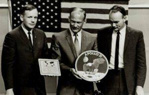 Posádka Apolla 11 (zleva Neil Armstrong, Edwin Aldrin a Michael Collins) poprvé ukazuje emblém mise letu; Neil Armstrong pak v ruce drží plaketu, která bude na lunárním modulu.