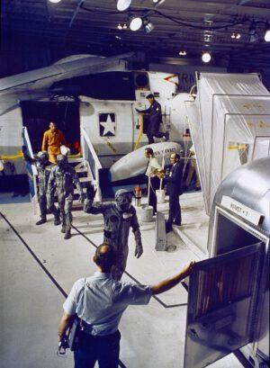 Posádka Apolla 11 přechází z vrtulníku do karantény v podpalubí USS Hornet