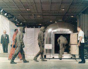 Armstrong, Collins a Aldrin vstupují do karantény, muž v oranžovém je lékař Bill Carpentier