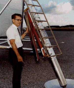 Technik Dave McCraw demonstruje odstranění krytu pouzdra nesoucího vlajku na lunárním modulu; zároveň je jasně vidět, kde a jak přesně byla vlajka na žebříku modulu umístěna.
