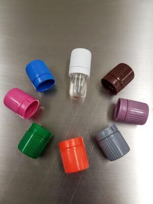 Průhledná lahvička se vzorkem experimentu Amyloid Aggregation. Různobarevná víčka se používají pro rozlišení odlišné délky inkubace.