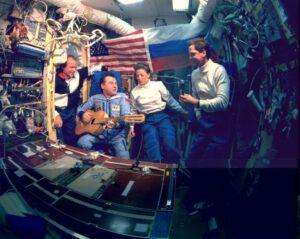 """Precourt, Strekalov, Dunbar a Harbough během chvíle volna na palubě Miru - tentokrát ovšem pouze """"jako"""" pro kameru IMAX. Bohužel, původní zvuková stopa byla pro dokument """"Mission to Mir"""" posléze nahrazena novou, takže filmový Strekalov hraje lépe než ve skutečnosti."""