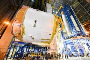 Překlápění motorovné sekce do vodorovné polohy. Na pravé straně fotografie je ve svářečce VAC vodíková nádrž pro druhou SLS (Artemis II).