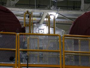 Instalace stříbrné fólie mezi motorem RS-25 č. 2 (vlevo) a 1 (vpravo). Předpokládá se, že fólie sníží potřebný rozsah renovace stupně po dokončení zážehového testu.