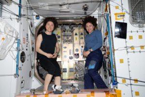 Christina Koch a Jessica Meir ukládají cubesaty do boxů umístěných na poklopu lodi Cygnus NG-12