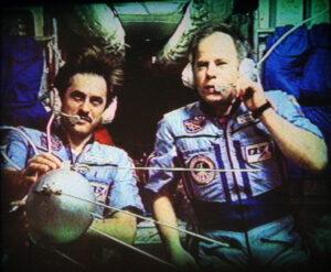 Vinogradov se Solovjovem během televizní reportáže předvádějí maketu Sputniku-1, kterou během výstupu vypustí do prostoru.
