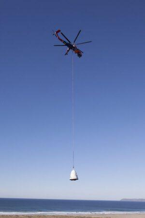 Archivní snímek testovací makety pro shozové zkoušky padáků zavěšené pod vrtulníkem.
