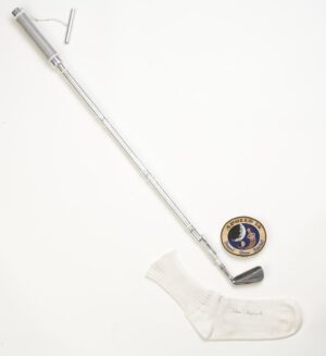 """Legendární """"šestka železo"""" včetně ponožky, v níž byla propašována, dnes odpočívá v muzeu Americké golfové asociace. Oba míčky se nacházejí kdesi v pahorkatině Fra Mauro na Měsíci..."""